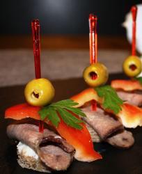 Канапе из языка, черного хлеба, масла, сл. оливки, болг. перца, зелени